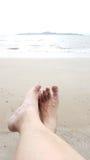 Ослабьте ног человека выше влажный пункт пляжа к морю Стоковые Изображения RF
