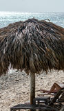 Ослаблять на пляже под деревянным зонтиком Стоковые Фотографии RF