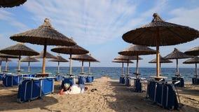 Ослабляющ на пустые sunbeds и зонтики песчаный пляж и море открытого моря Стоковое Фото