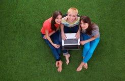 3 ослабляя красивых flirting женщины сидят на зеленой траве Стоковое фото RF