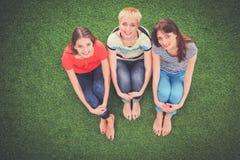 3 ослабляя красивых flirting женщины сидят на зеленой траве Стоковая Фотография RF