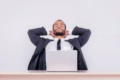 ослабляя работа Усмехаясь африканский бизнесмен сидя на столе Стоковое Изображение RF