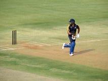 Отбивающий мяч принимая бег, смотря позади стоковое изображение rf