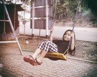 Отбрасывать счастливого ребенка сидя на качании на внешнем стоковые фотографии rf