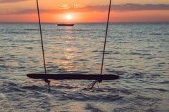 Отбросьте на тропическом пляже против захода солнца Деревянное hangi качания Стоковые Изображения