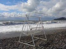 Отбросьте на Pebble Beach, брызгающ волны и красивые облака Стоковые Изображения RF