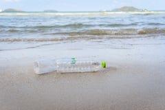 Отброс в море с пластиковой бутылкой на море пляжа песочном грязном на острове стоковые изображения rf