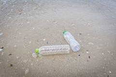 Отброс в море с пластиковой бутылкой на море пляжа песочном грязном на острове - проблема окружающей среды пластикового загрязнен стоковое фото