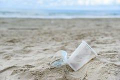 Отброс в море с пластиковой бутылкой, пластиковой чашкой и коробкой пены на море пляжа песочном грязном стоковое изображение