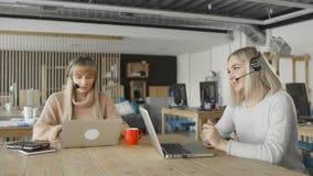 Отбуксируйте шлемофоны носки женщины говоря смотрящ ноутбук, женский менеджер работы с клиентом skyping акции видеоматериалы