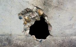 Отверстие в бетонной стене разрушения, пулевое отверстие, абстрактный открытый космос предпосылки для дизайна Стоковое фото RF