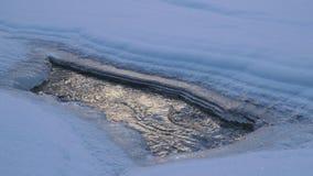 Отверстие в льде на замороженном реке на холодный зимний день видеоматериал