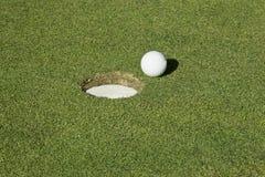 отверстие гольфа шарика рядом с Стоковое Изображение