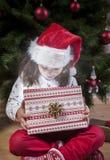 Отверстие маленькой девочки он представляет под рождественской елкой Стоковые Изображения