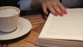 Отверстие молодой женщины и чтение книги пока выпивающ кофе в уютном кафе Дама дела читая книгу r Изучать f сток-видео