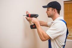 Отверстие рабочий-строителя сверля в стене стоковые изображения