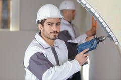Отверстие уверенно работника сверля в стене Стоковое фото RF