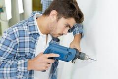 Отверстия мужского построителя сверля в стене на строительной площадке стоковое фото rf