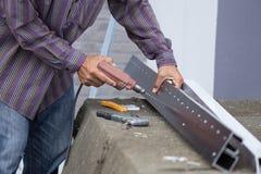 Отверстия работника сверля в алюминиевой рамке конструкции с избирают Стоковые Изображения RF