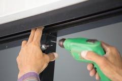 Отверстия работника сверля в алюминиевой рамке конструкции с избирают Стоковое Изображение RF