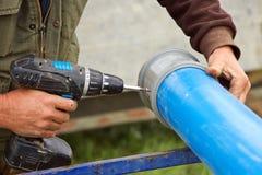 Отверстия работника сверля на пластичной трубе водопровода Стоковая Фотография RF