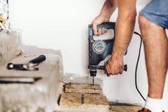 Отверстия рабочий-строителя сверля в деревянной доске и бетоне используя профессиональное машинное оборудование Стоковые Изображения RF