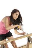Отвертка молодой женщины кладя винт в древесину Стоковое фото RF