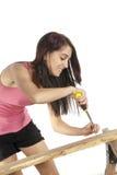 Отвертка молодой женщины кладя винт в древесину Стоковые Фотографии RF