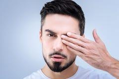 Ответственный молодой пациент проверяя его зрение в местной больнице Стоковые Изображения
