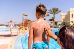 Ответственный солнцезащитный крем затирания матери на ее сыне стоковое фото