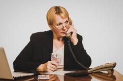 Ответ зрелой коммерсантки ждать на телефоне с деньгами Стоковые Фотографии RF
