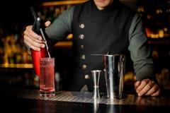 Отделка бармена подготавливая коктеиль на счетчике бара Стоковое Фото