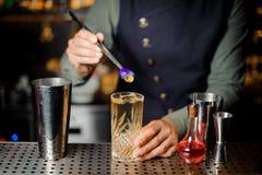Отделка бармена подготавливая коктеиль с фиолетовым цветком Стоковая Фотография RF