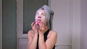 Отделка женщин прикладывая лицевую маску сток-видео
