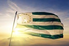 Отдел Caqueta ткани ткани ткани флага Колумбии развевая на верхнем тумане тумана восхода солнца бесплатная иллюстрация