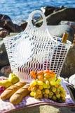 Отдохните морем с виноградинами, яблоками, грушами, багетами, вином и корзиной на покрывале Стоковое Изображение