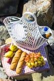 Отдохните морем с виноградинами, яблоками, грушами, багетами, вином и корзиной на покрывале Стоковые Фото