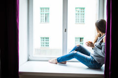 Отдыхая и думая женщина Спокойная девушка при чашка чаю или кофе сидя и выпивая на окн-силле дома Стоковые Фотографии RF