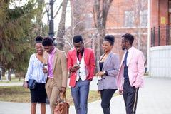 Отдых и подростковая концепция группа в составе счастливые друзья гуляя на улице стоковое фото