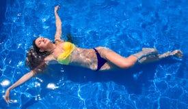 Отдых лета, девушка ослабляя в бассейне стоковая фотография
