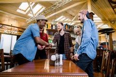 Отдых, люди и концепция праздников - группа в составе 5 молодых multiracial усмехаясь друзей имея встречу в кафе стоковые изображения