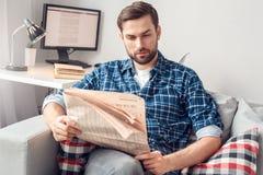 Отдых молодого человека дома сидя газета чтения ослабил стоковые изображения