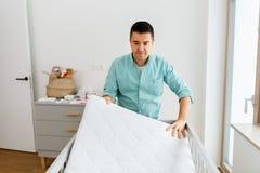 Отец аранжируя кровать младенца с тюфяком дома стоковые фотографии rf