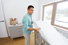 Отец аранжируя кровать младенца с тюфяком дома стоковое фото rf