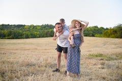 Счастливая молодая семья Отец, беременная мать, и 2 меньших сынов на их задних частях Скошенное пшеничное поле на предпосылке E стоковые изображения rf