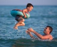 Отец бросает вверх его сынка в раздувном круге под море Стоковые Изображения RF