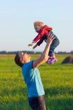 Отец бросает его счастливого младенца в небе Влюбленность и счастье стоковые изображения rf