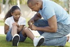 Отец вставляя повязку к колену дочери на парке Стоковое Фото