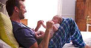 Отец в кровати играя с Newborn дочерью младенца акции видеоматериалы