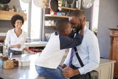 Отец говоря до свидания к сыну по мере того как он выходит для работы стоковое изображение